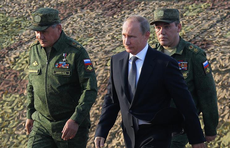 Vladimir Putin and Russian Defense Minister Sergei Shoigu (left)