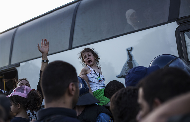 Migrants trying to board a bus, at the border between Serbia and Croatia