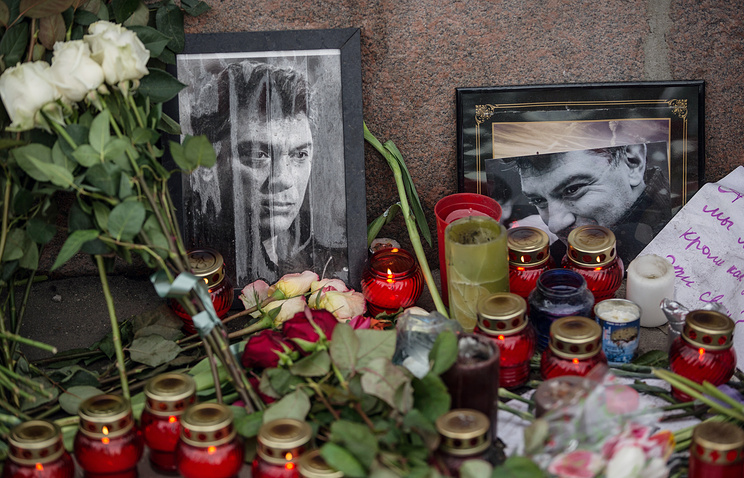 Flowers and candles left at a portrait of Russia's opposition politician Boris Nemtsov murdered in central Moscow
