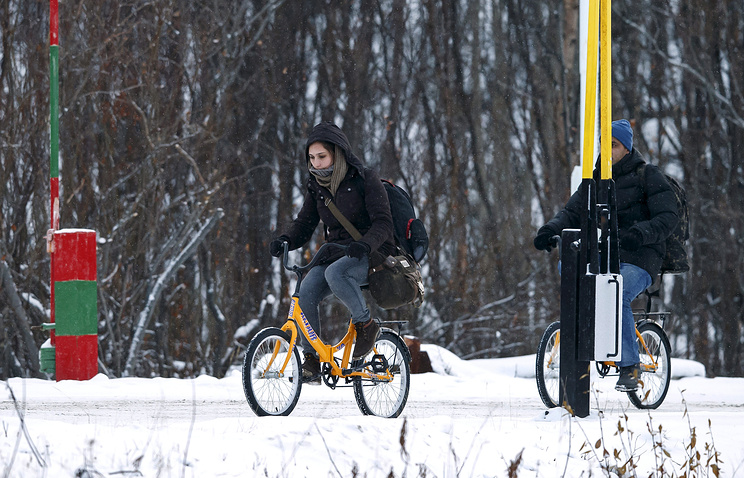 Two refugees use bikes to cross the border between Norway and Russia