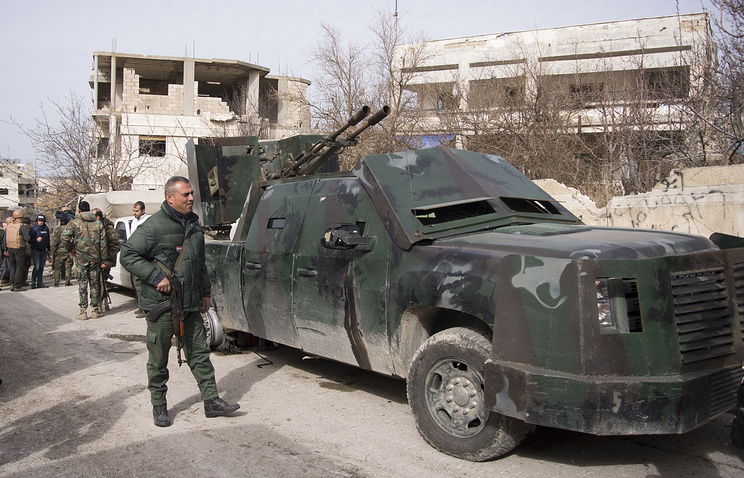 Syrian soldiers stand at a pickup truck with a gun mounted on top (archive)