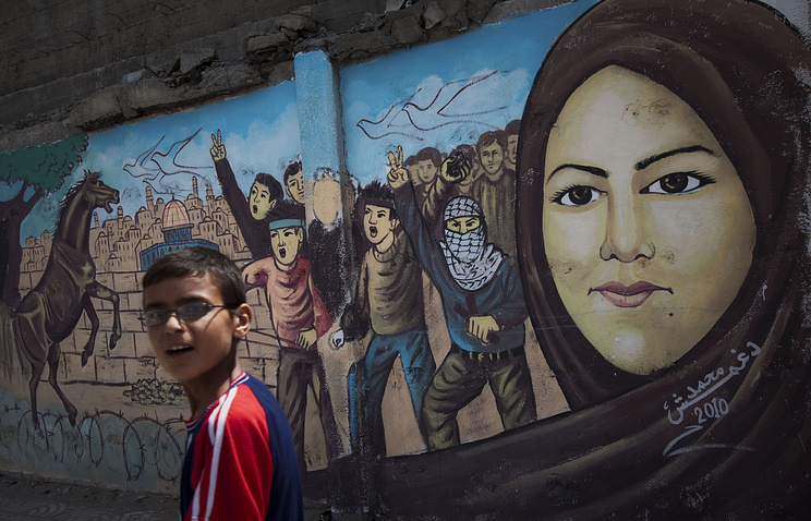 Palestinian boy walks past a graffiti in Gaza City