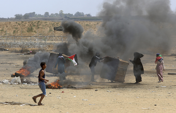 Palestinian protesters burn tires near the Israeli border fence, in the Gaza Strip