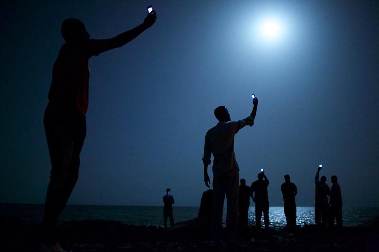 Африканские мигранты ночью в городе Джибути держат в поднятых вверх руках мобильные телефоны, пытаясь поймать дешевый сигнал из соседней Сомали – ниточку, связывающую их с родственниками за рубежом.