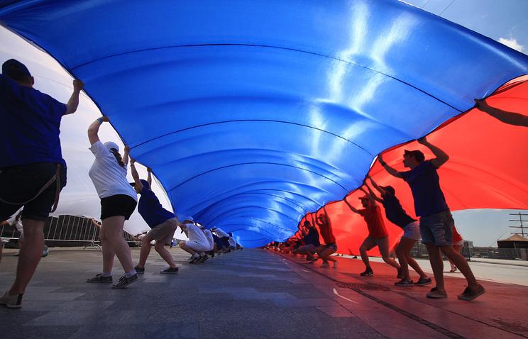 Россия, Крым,  Ялта. Участники праздничных мероприятий в честь Дня России разворачивают большой российский флаг на площади Ленина 12 июня 2014 года