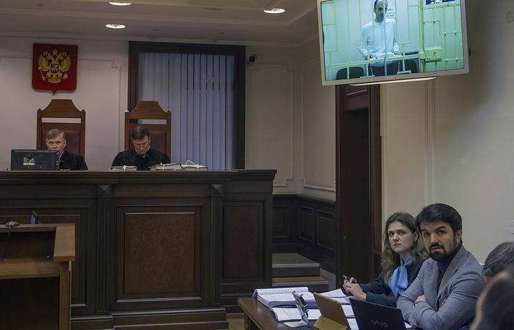 Юсуп Темирханов (на экране), осужденный за убийство бывшего командира 160-го гвардейского танкового полка Юрия Буданова, и его адвокат Мурад Мусаев (справа)