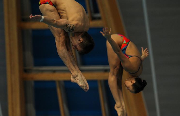 Российские спортсмены Надежда Бажина и Виктор Минибаев выступают на соревнованиях по синхронным прыжкам в воду с трехметрового трамплина