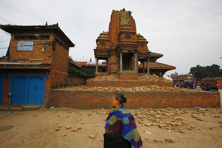 A Nepalese woman walks past a collapsed temple in Bhaktapur Durbar Square after an earthquake in Kathmandu, Nepal, Sunday, April 26, 2015 .A strong magnitude earthquake shook Nepal's capital and the densely populated Kathmandu Valley before noon Saturday, causing extensive damage with toppled walls and collapsed buildings, officials said. (AP Photo/Niranjan Shrestha)