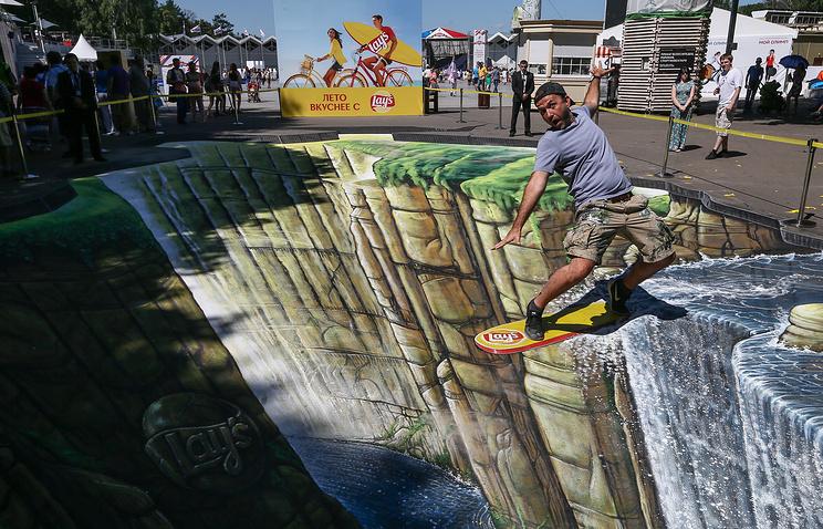 """Лондонский художник Джо Хилл у своего 3D-рисунка на асфальте в парке """"Сокольники"""""""