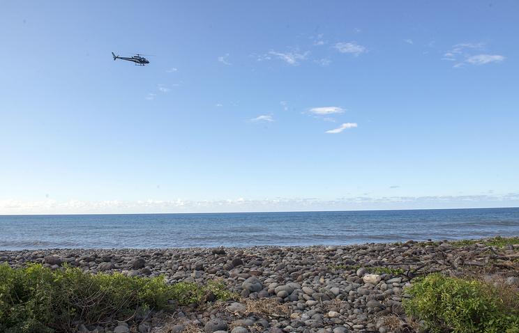 Вертолет над пляжем острова Реюньон в поисках новых обломком