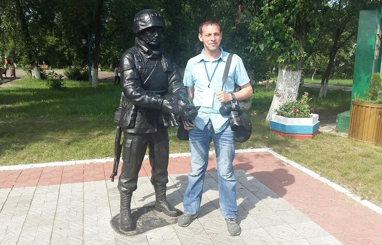 Фотограф ТАСС Александр Рюмин рядом с памятником, отлитым по его кадру