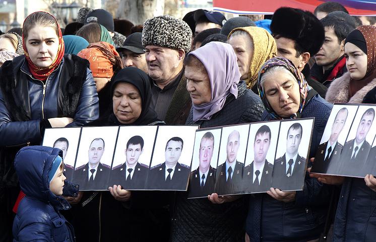 """Участники митинга против терроризма на площади у мечети """"Сердце Чечни"""" с портретами погибших в результате теракта в Грозном, 13 декабря 2014 года"""