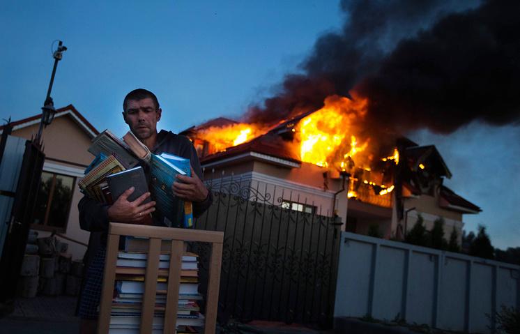 Пожар в жилом доме в селе Николаевка в результате минометного обстрела пригородных районов Луганска, июль 2014 года